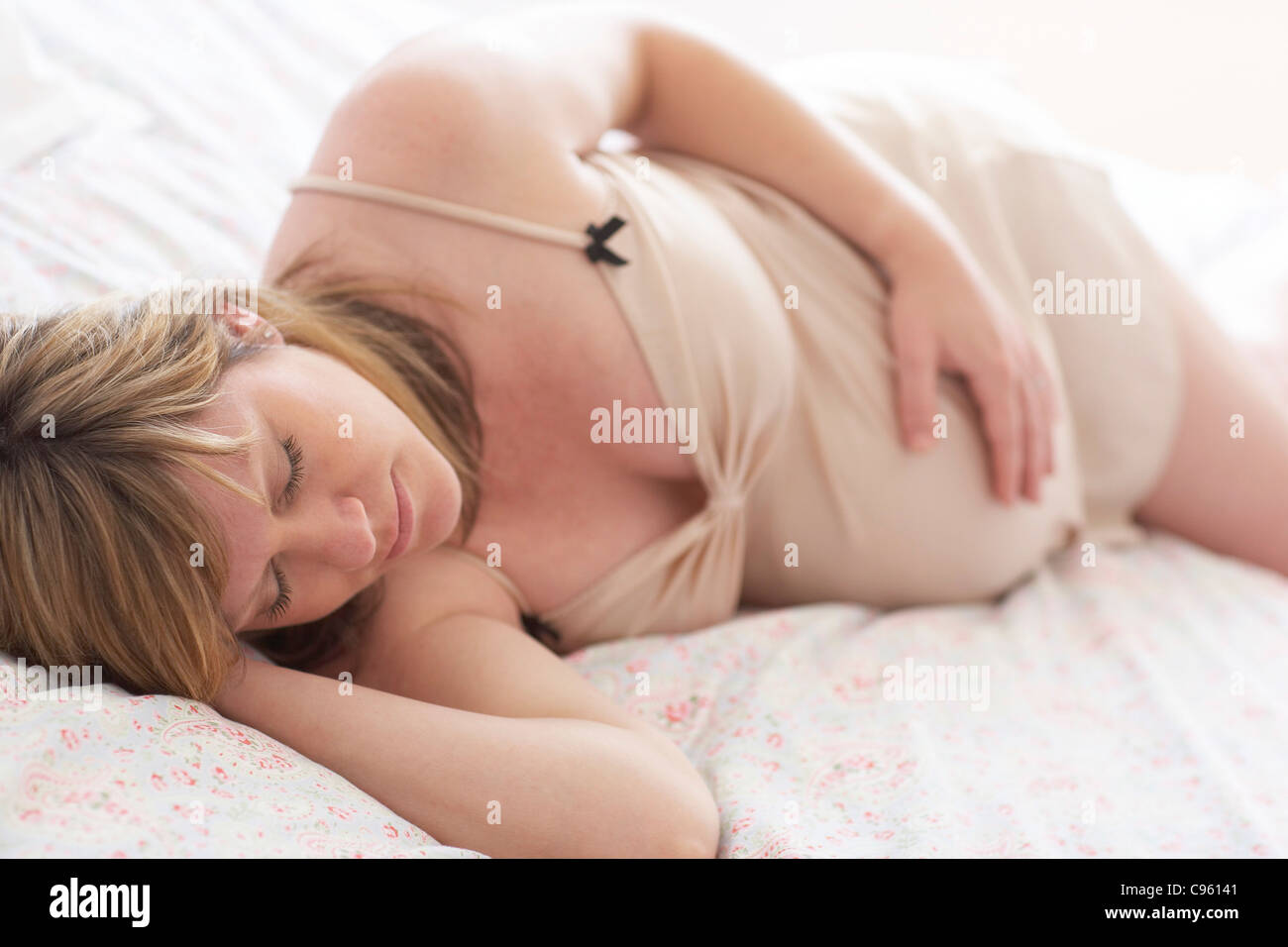 Pregnant woman sleeping. She is 35 weeks pregnant. - Stock Image