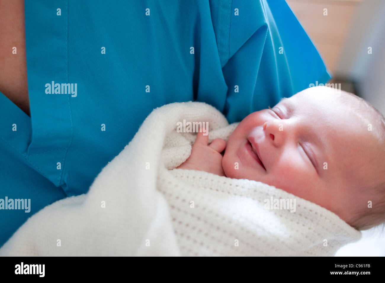 Newborn baby held by a nurse. - Stock Image