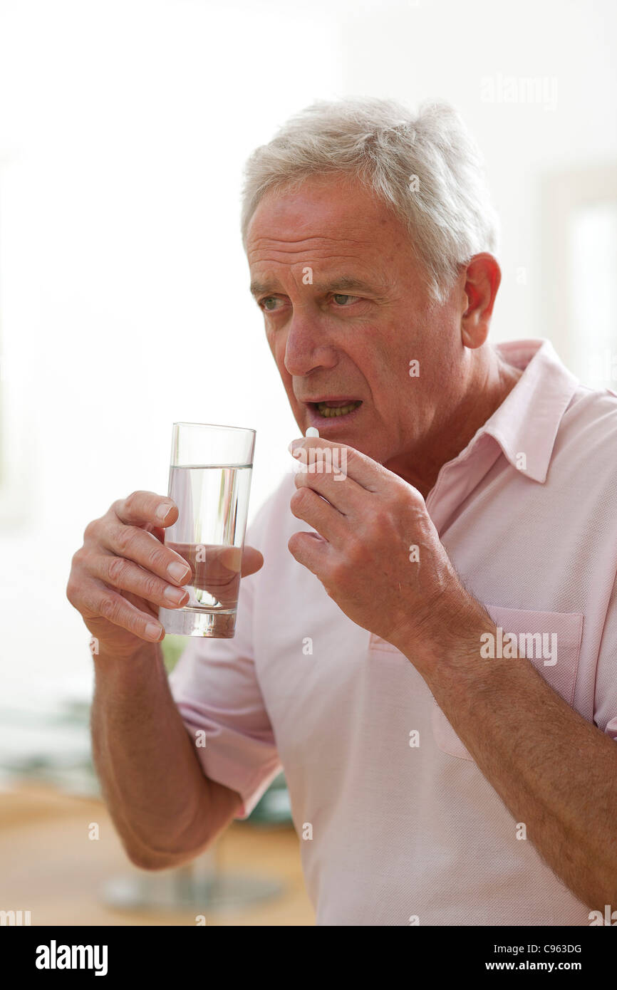 Man taking a pill. - Stock Image