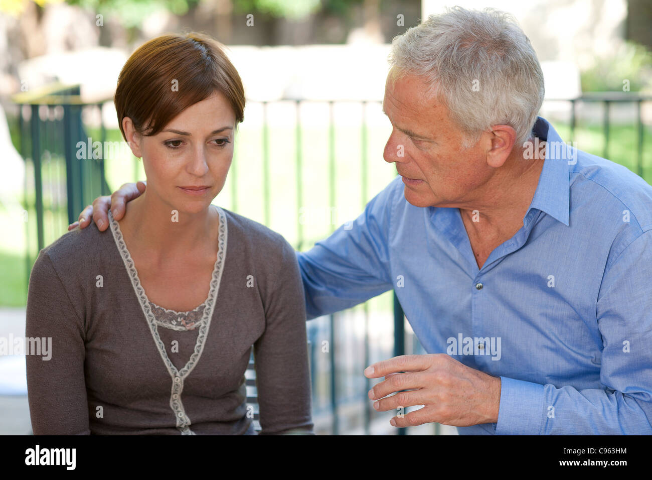 Absence seizure. Man looking after a woman who is having an absence seizure. - Stock Image