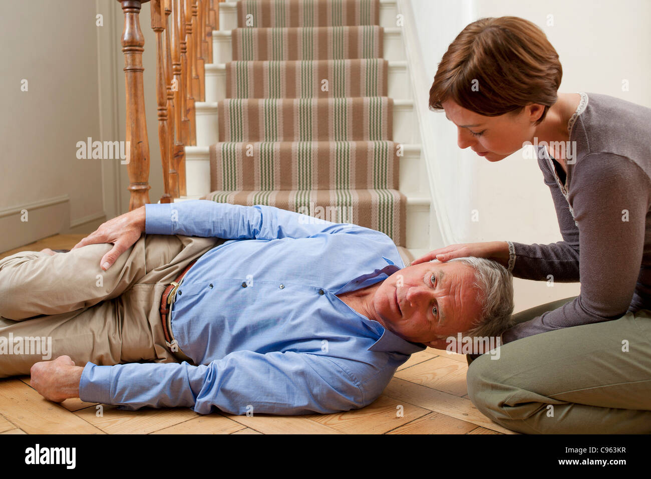 Senior man injured in a fall being placed in the recovery position. - Stock Image