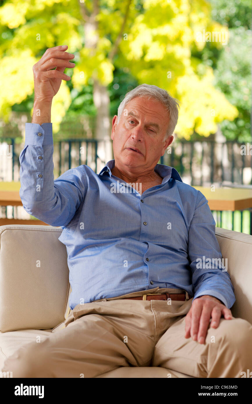 Senior man having a stroke. He is only able to raise one arm not both because of the stroke. - Stock Image