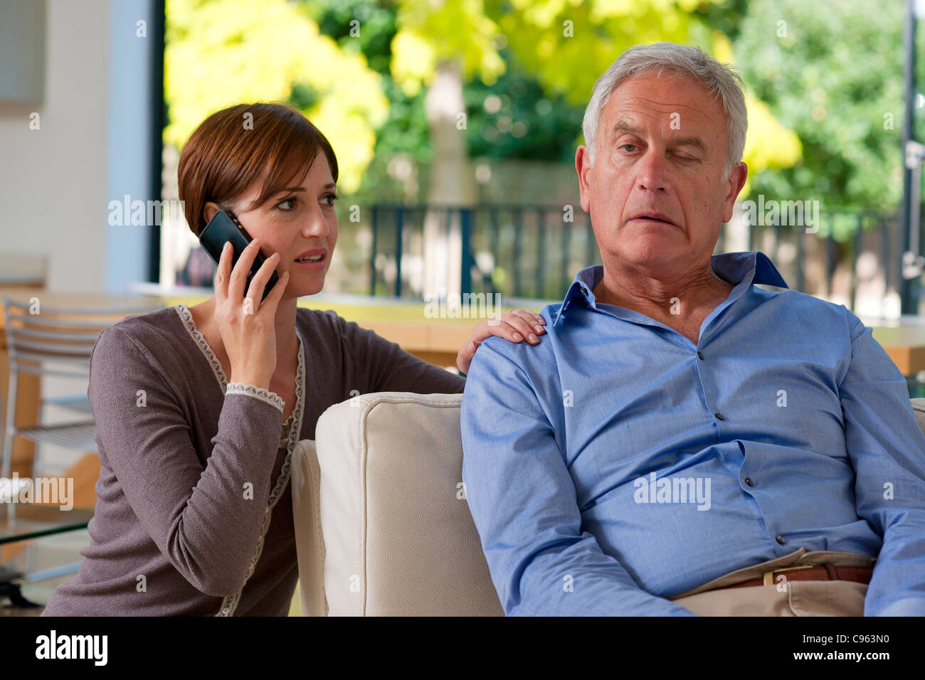 Senior man having a stroke. He is experiencing facial weakness. A woman is phoning for an ambulance. - Stock Image