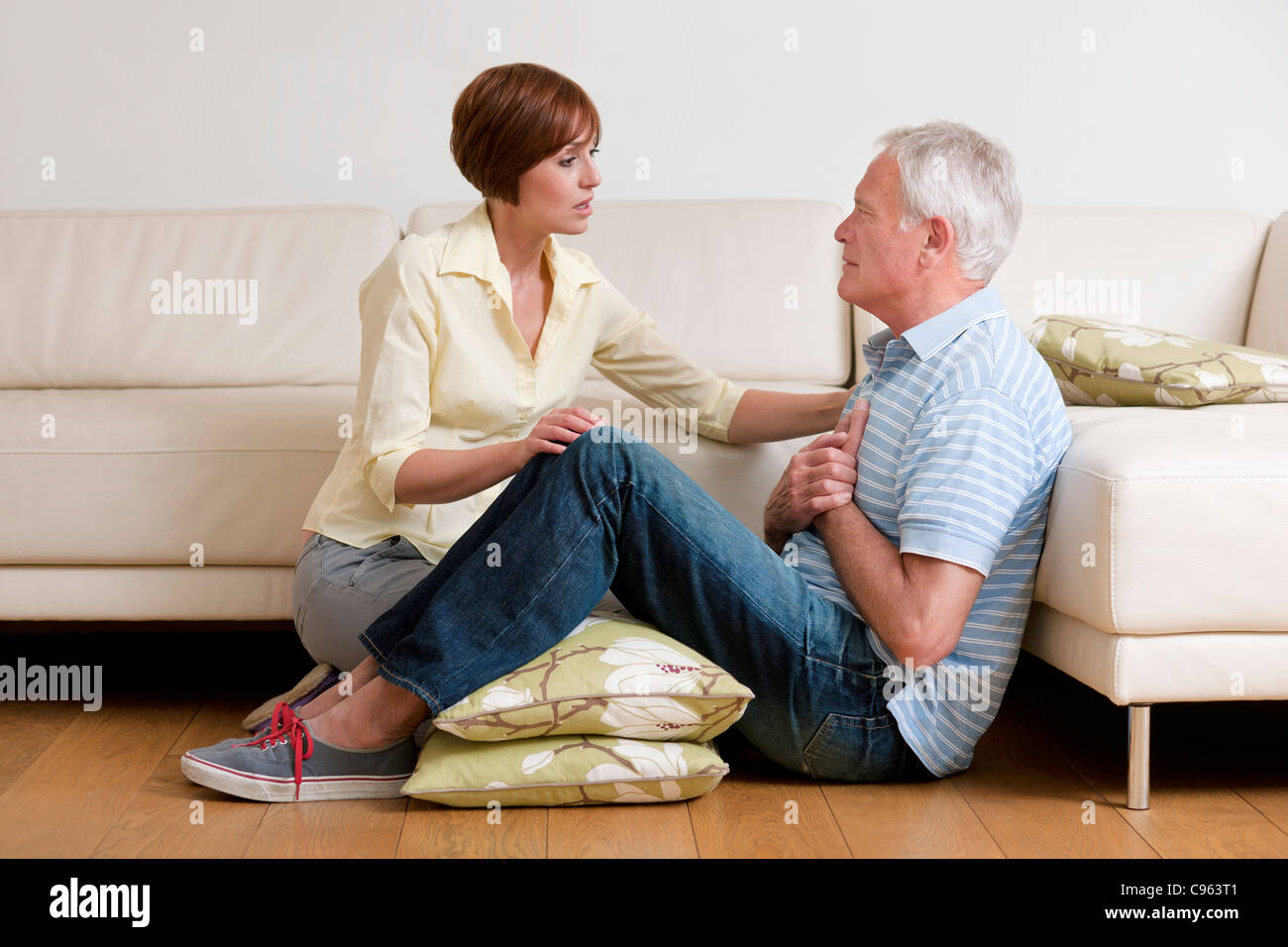 Man having a heart attack. The woman is placing him in a comfortable position until help comes. - Stock Image
