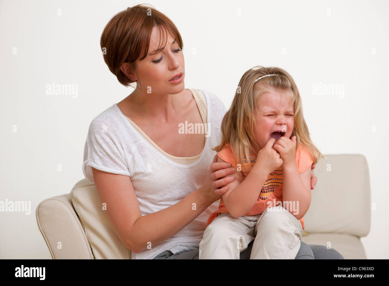 Toddler crying on her mother's lap. - Stock Image
