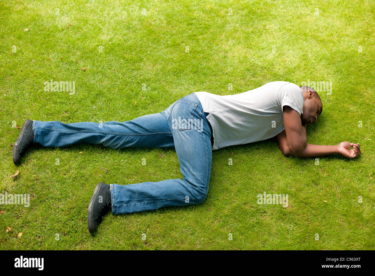 Man in recovery position. - Stock Image