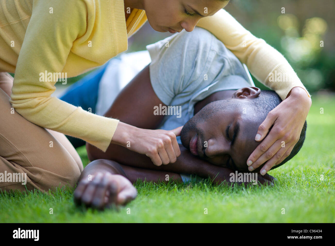 Recovery position. Man being placed in the recovery position. - Stock Image