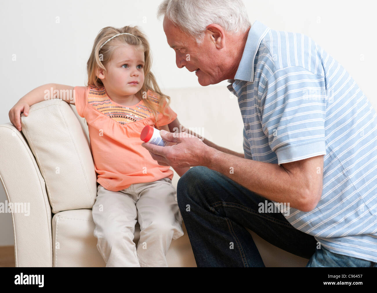 First aid for poisoning. Man asking a young girl if she has swallowed some pills. - Stock Image