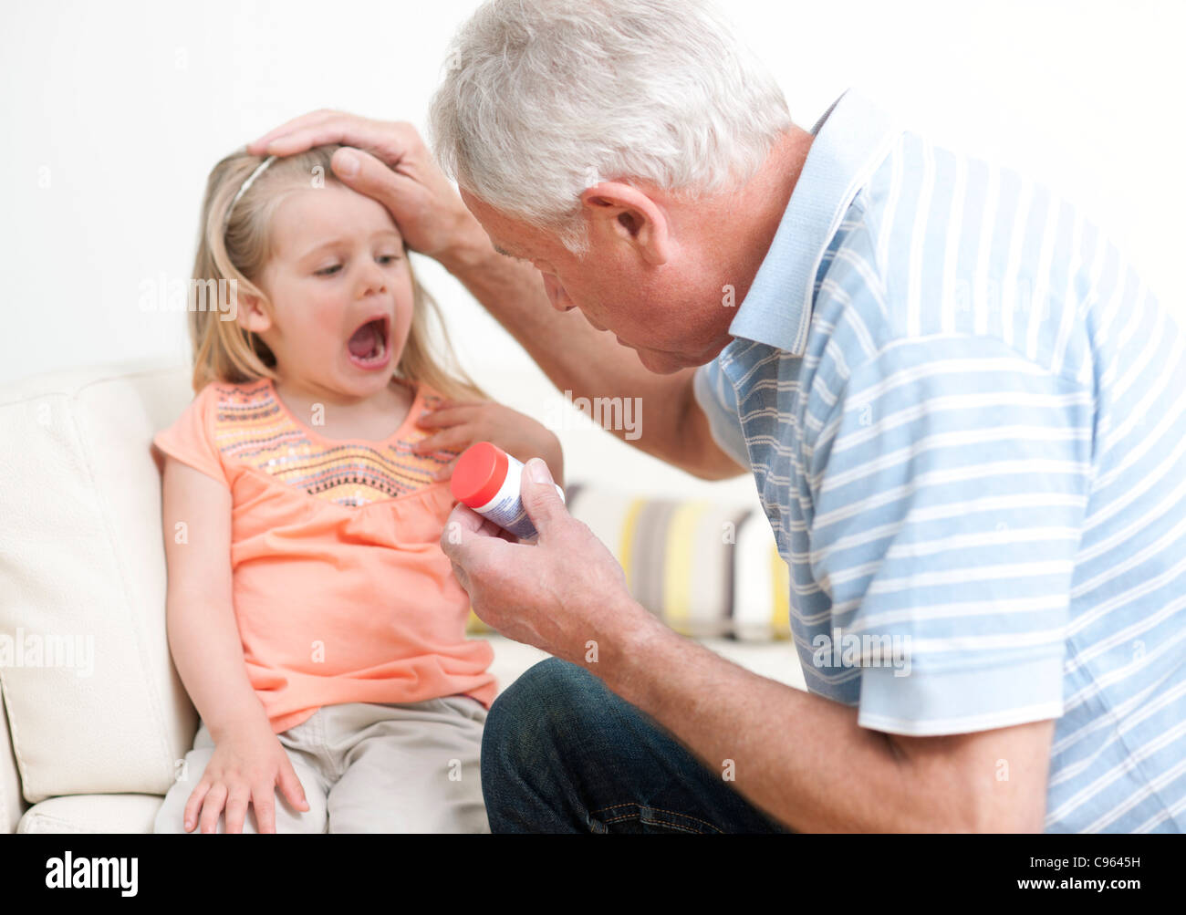 First aid for poisoning. Man checking a a young girl's mouth for pills. - Stock Image