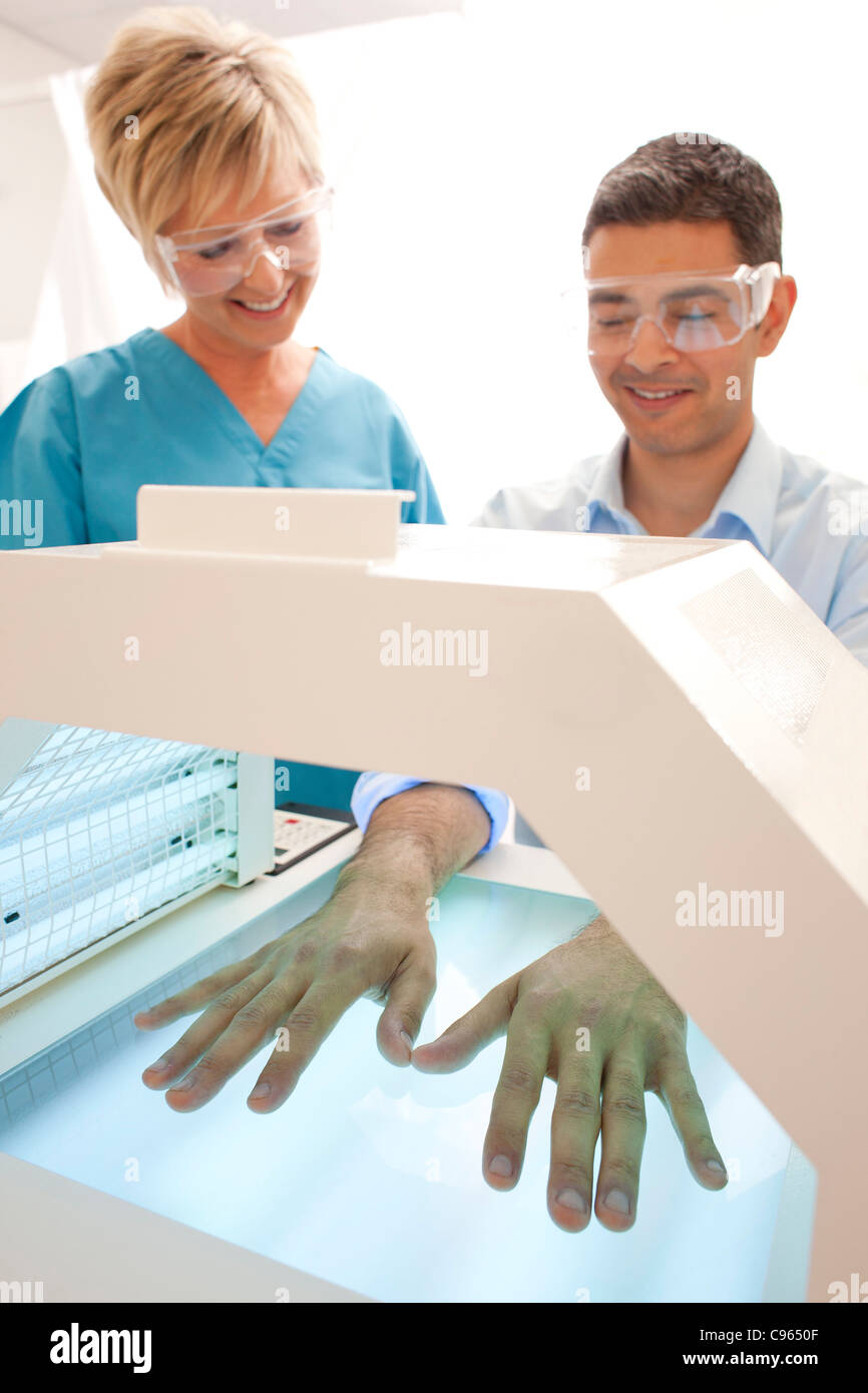 Phototherapy booth. Patient with their hands in a phototherapy box. - Stock Image
