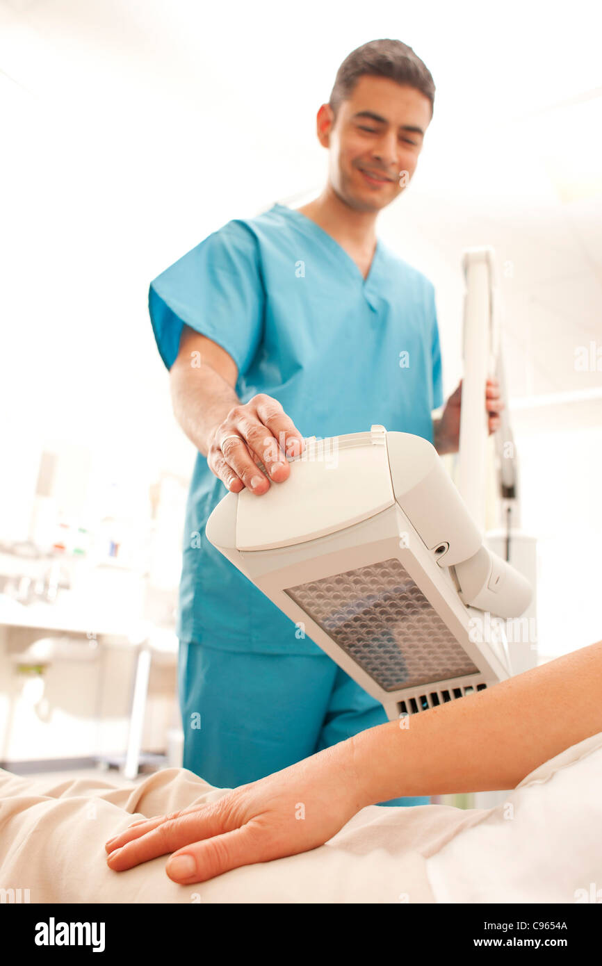 Photodynamic therapy. Dermatologist positioning a photodynamic therapy lamp over a patient. - Stock Image
