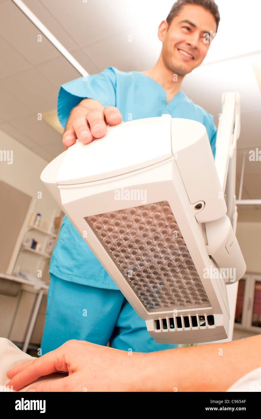 Photodynamic therapy. Dermatologist positioning a photodynamic therapy lamp over a patient. - Stock Image