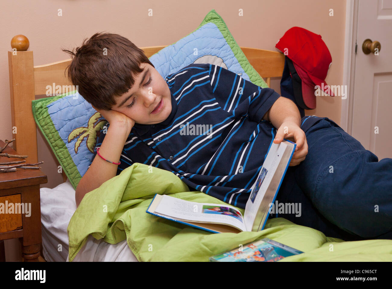 Autistic boy, age 13, reading on bed. - Stock Image
