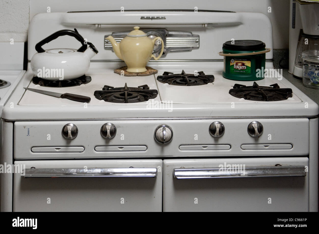 Retro white stove and oven in a kitchen with a yellow teapot on the burner - Stock Image