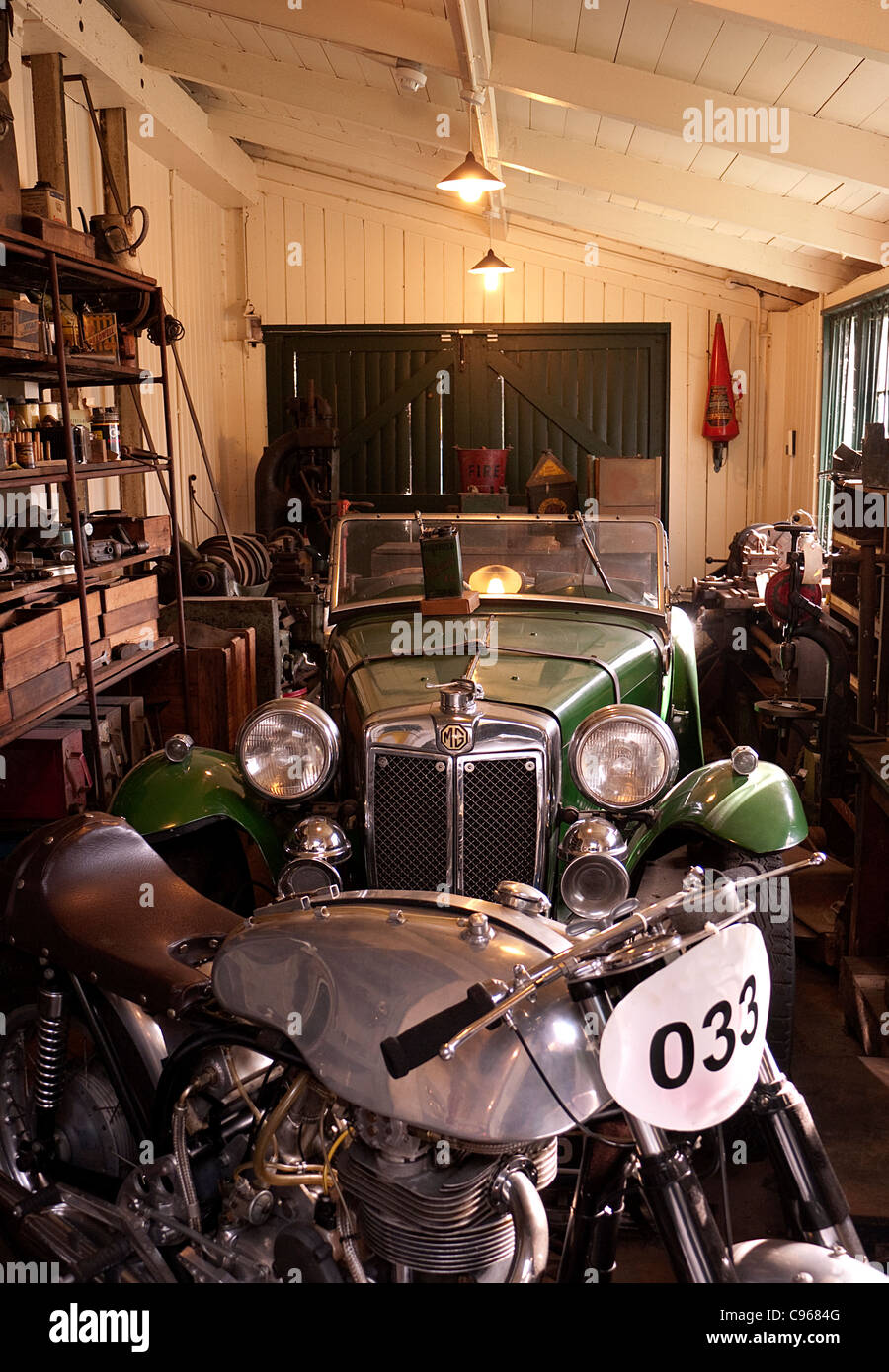 Classic car garage with 1930's MG car and motorcycle - Stock Image