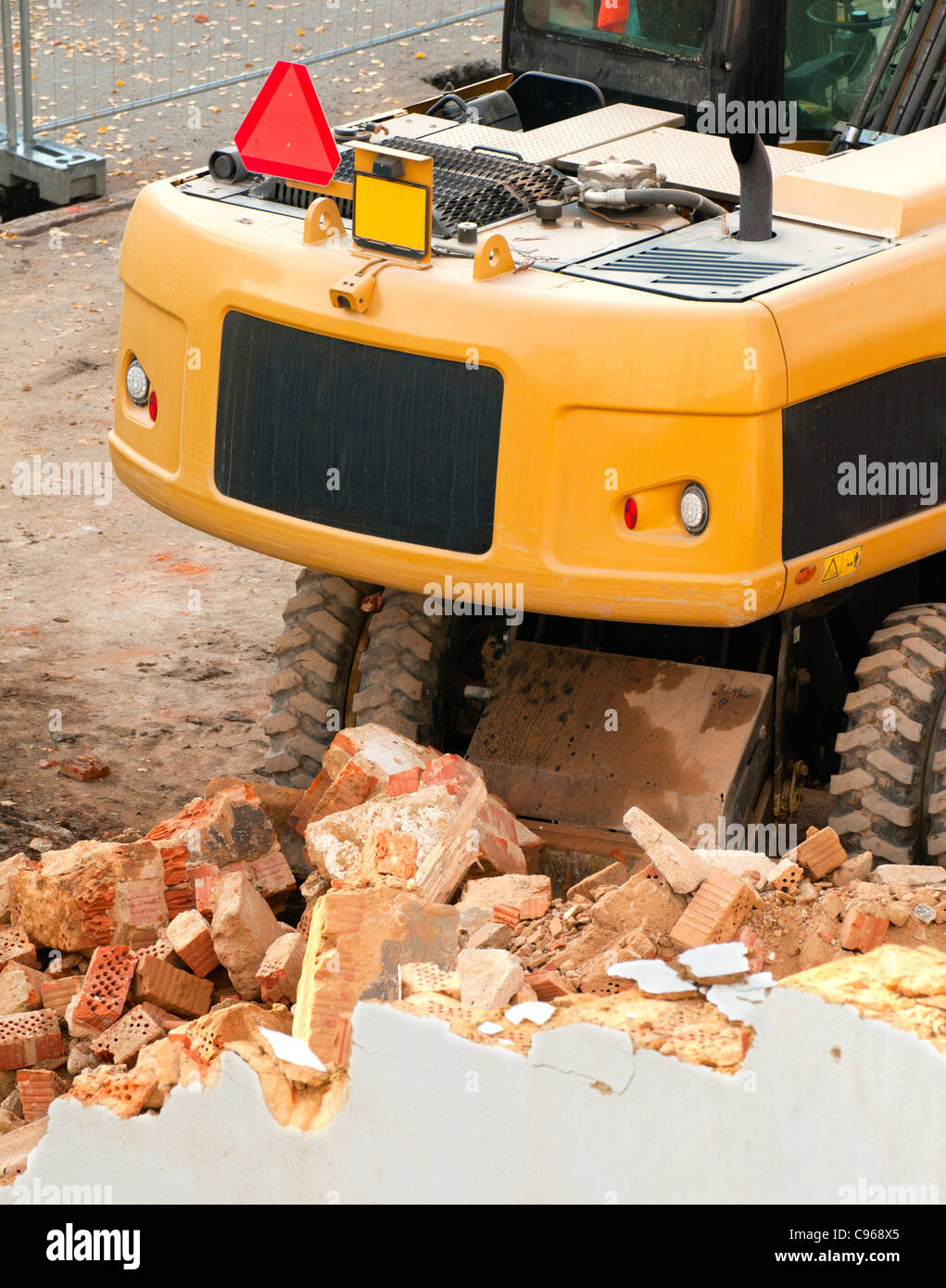 Detail of Yellow Digger Near Building Under Demolition - Stock Image