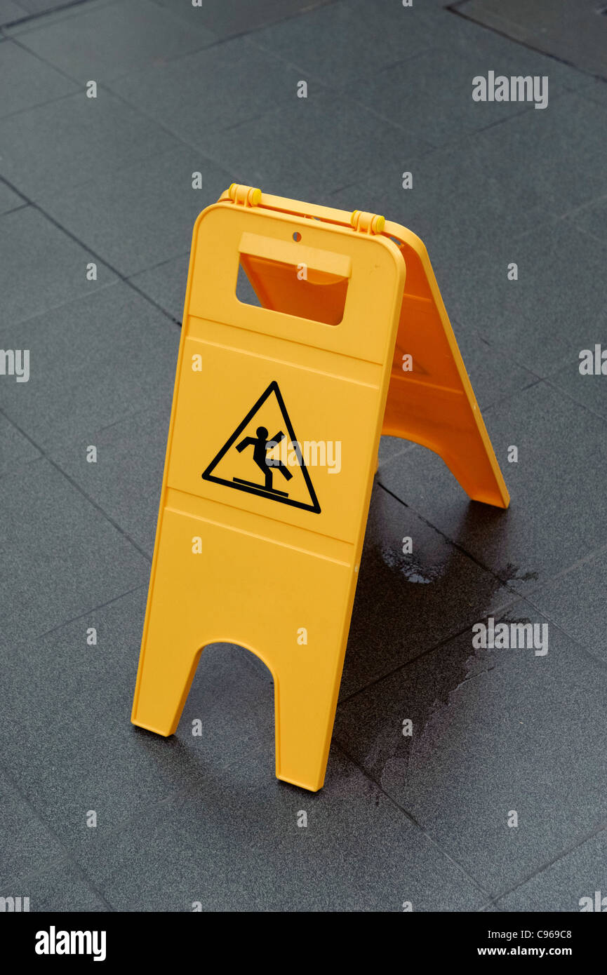 Bright yellow slippery floor warning sign - Stock Image