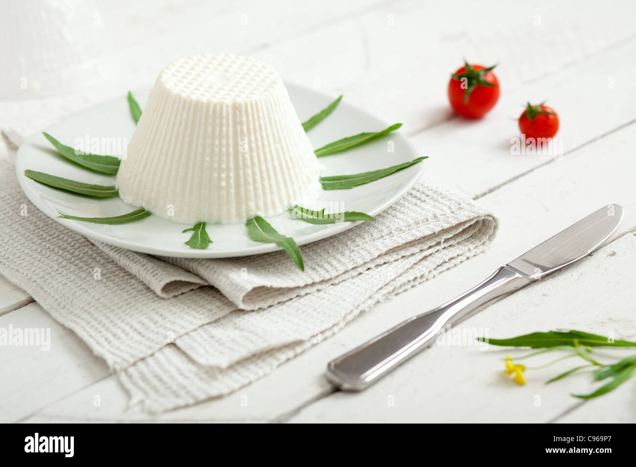 Ricotta, a Typical Italian Dairy Product, with Rocket, Cherry Tomatoes and a Knife - Stock Image