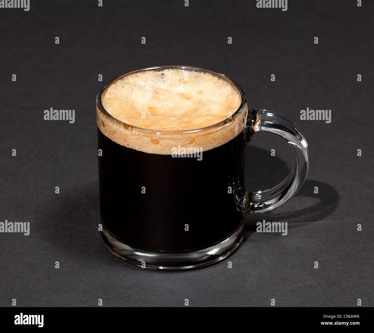 Black expresso coffee with heady froth in a glass mug or cup - Stock Image