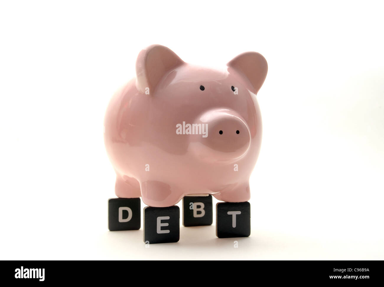 PIGGY BANK ON LETTERS SPELLING 'DEBT' RE FINANCIAL CRISIS SAVINGS ECONOMY ECONOMIC DOWNTURN MONEY  BANKS - Stock Image
