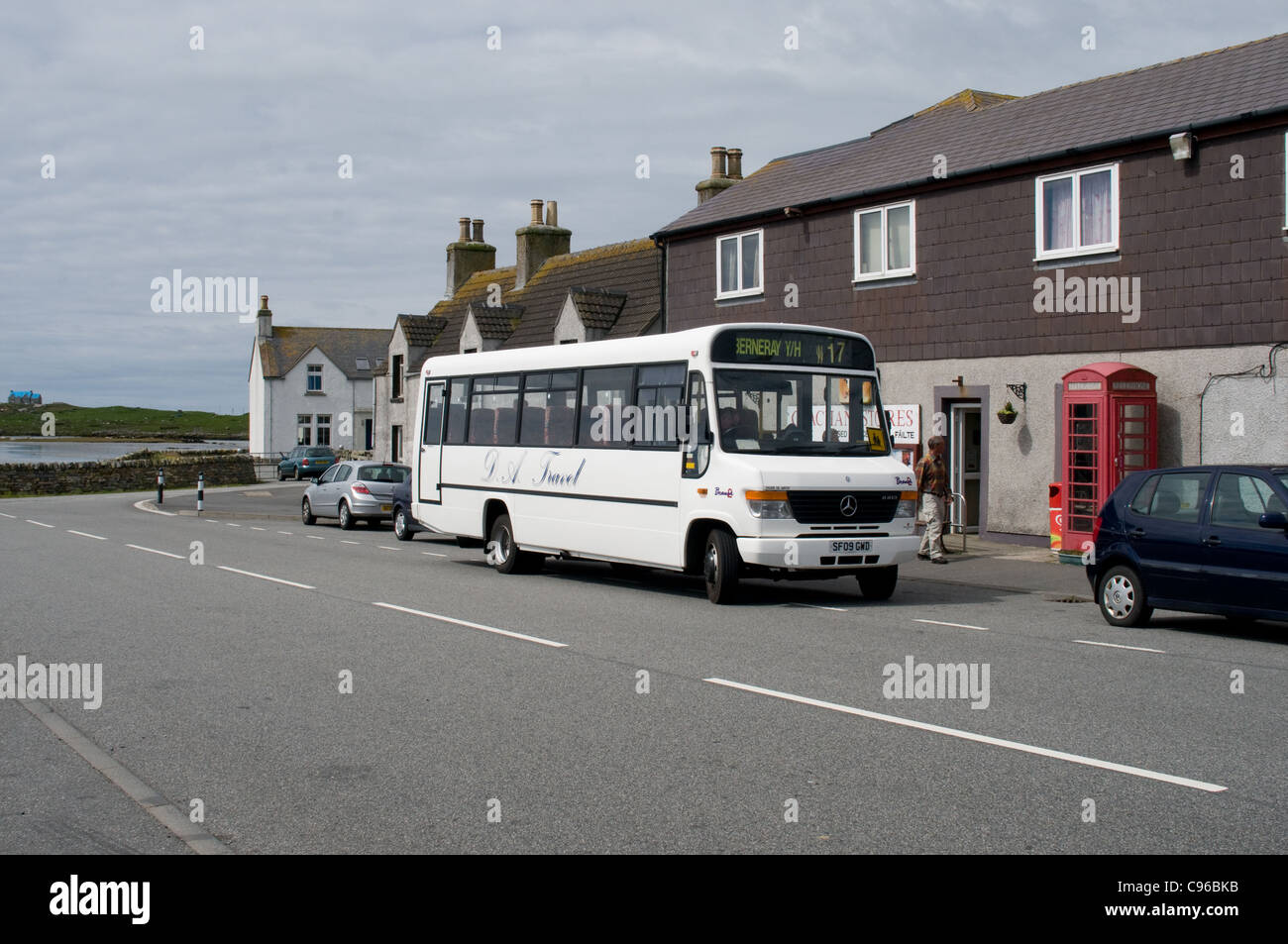 A Mercedes-Benz minibus operated by D A travel waites in Berneray before continuing its journey. - Stock Image