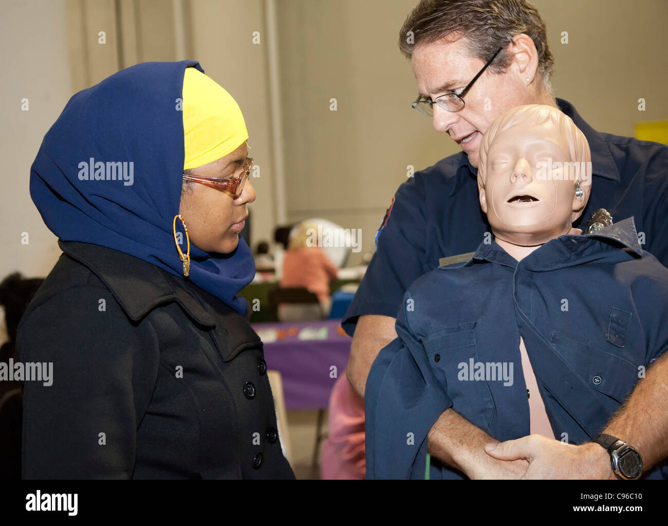 Detroit, Michigan - An emergency medical technician teaches the Heimlich maneuver to a person attending a community - Stock Image