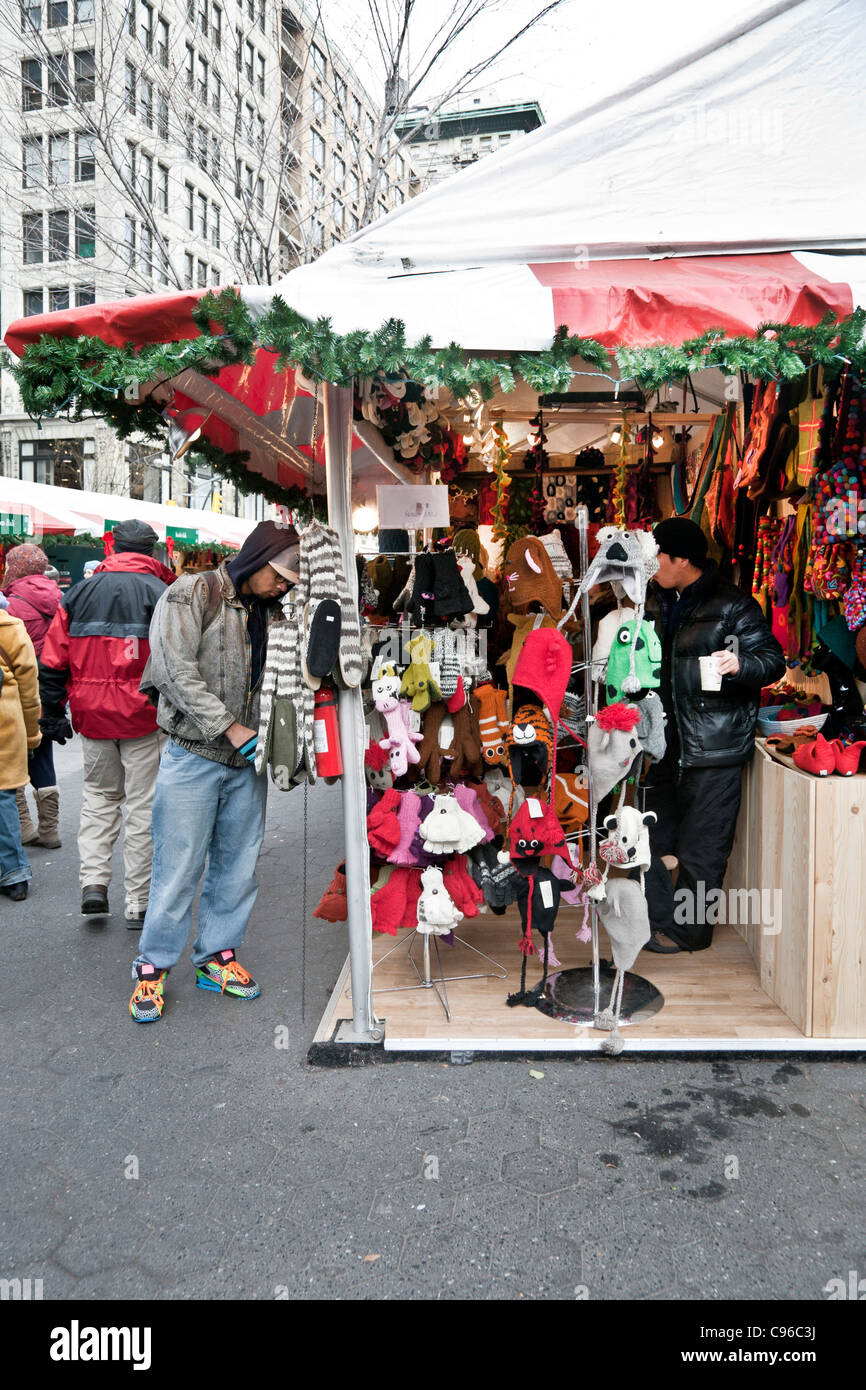 diverse multiethnic crowd warmly dressed shoppers browse gift items at outdoor holiday Christmas market shops in - Stock Image