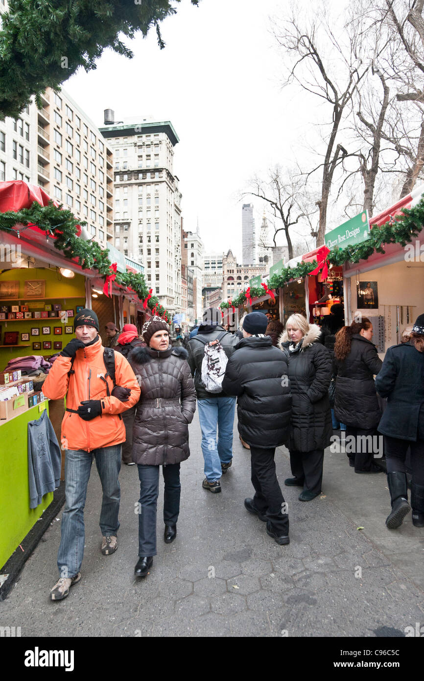 warmly dressed tourist couple mingles with crowd browsing outdoor shops at popular outdoor holiday Christmas market - Stock Image
