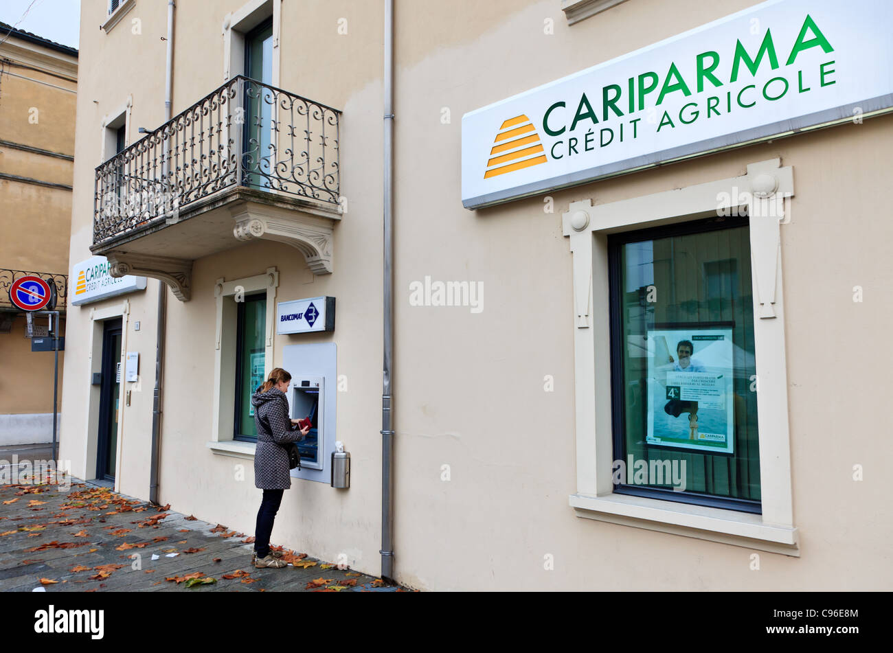 Woman using a cash machine, Sissa, Italy - Stock Image