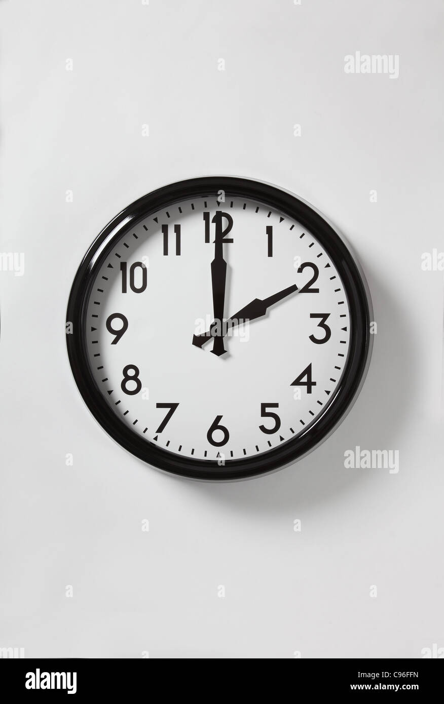 A wall clock with the time at 2 o'clock - Stock Image