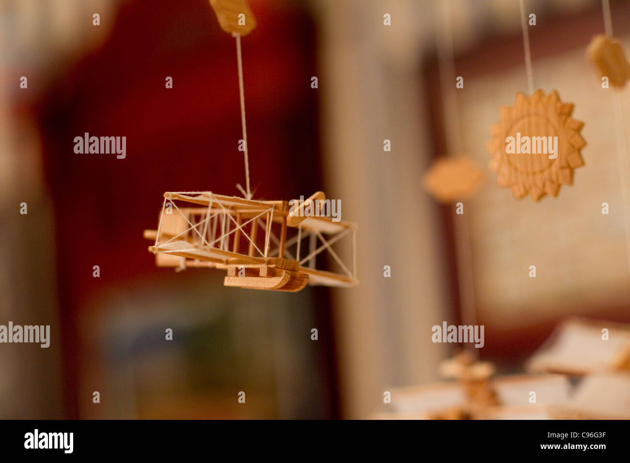 A wooden bi-plane hanging from a mobile in a children's bedroom. - Stock Image
