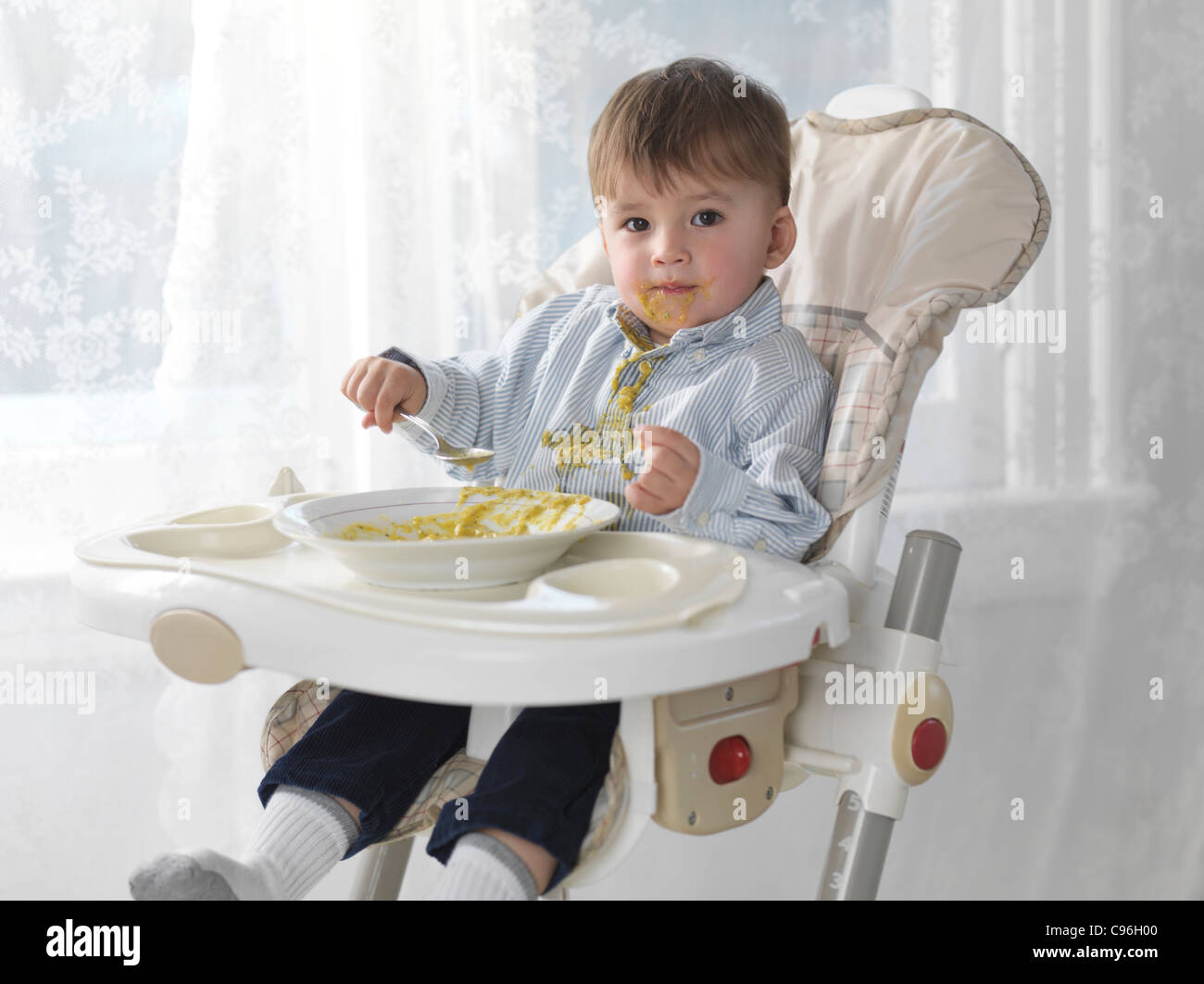 One and a half year old boy sitting in a high chair and eating soup with a spoon, spilling it on his shirt - Stock Image