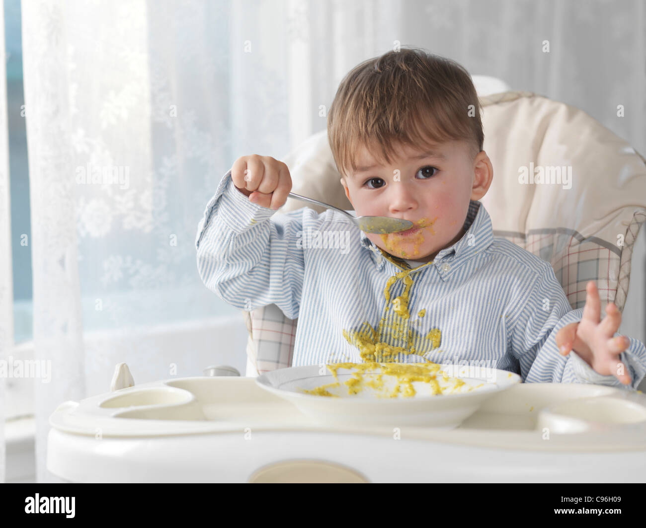 Cute baby boy sitting in a high chair and eating soup with a spoon, spilling it on his shirt - Stock Image