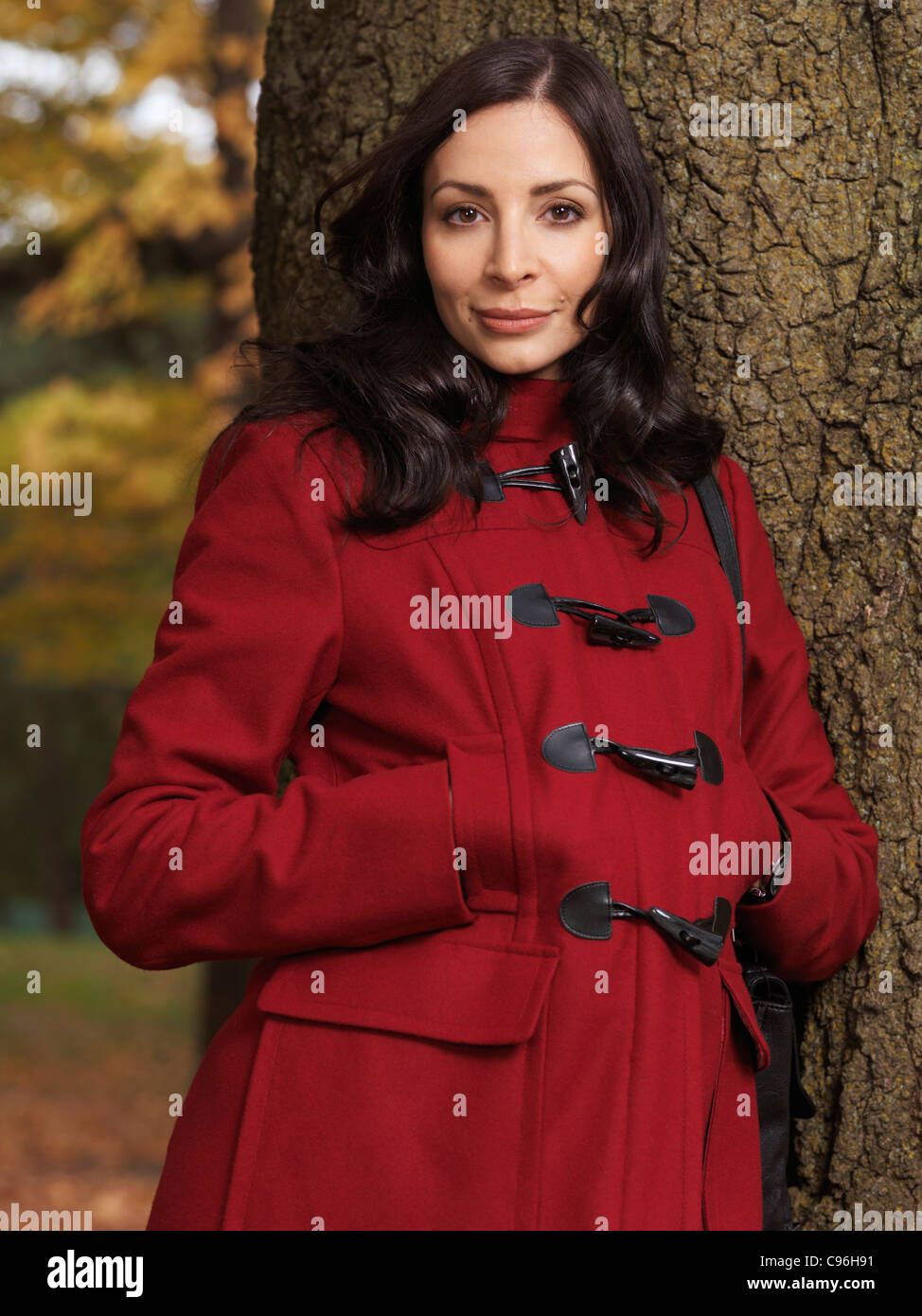 Portrait of a beautiful woman in red fashionable coat leaning against a tree - Stock Image