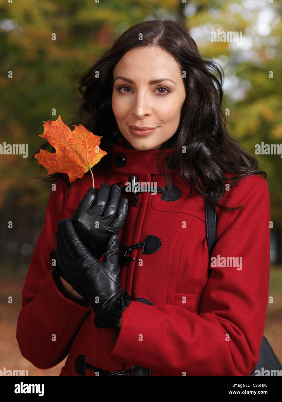 Portrait of a beautiful woman holding a red maple leaf in her hands - Stock Image