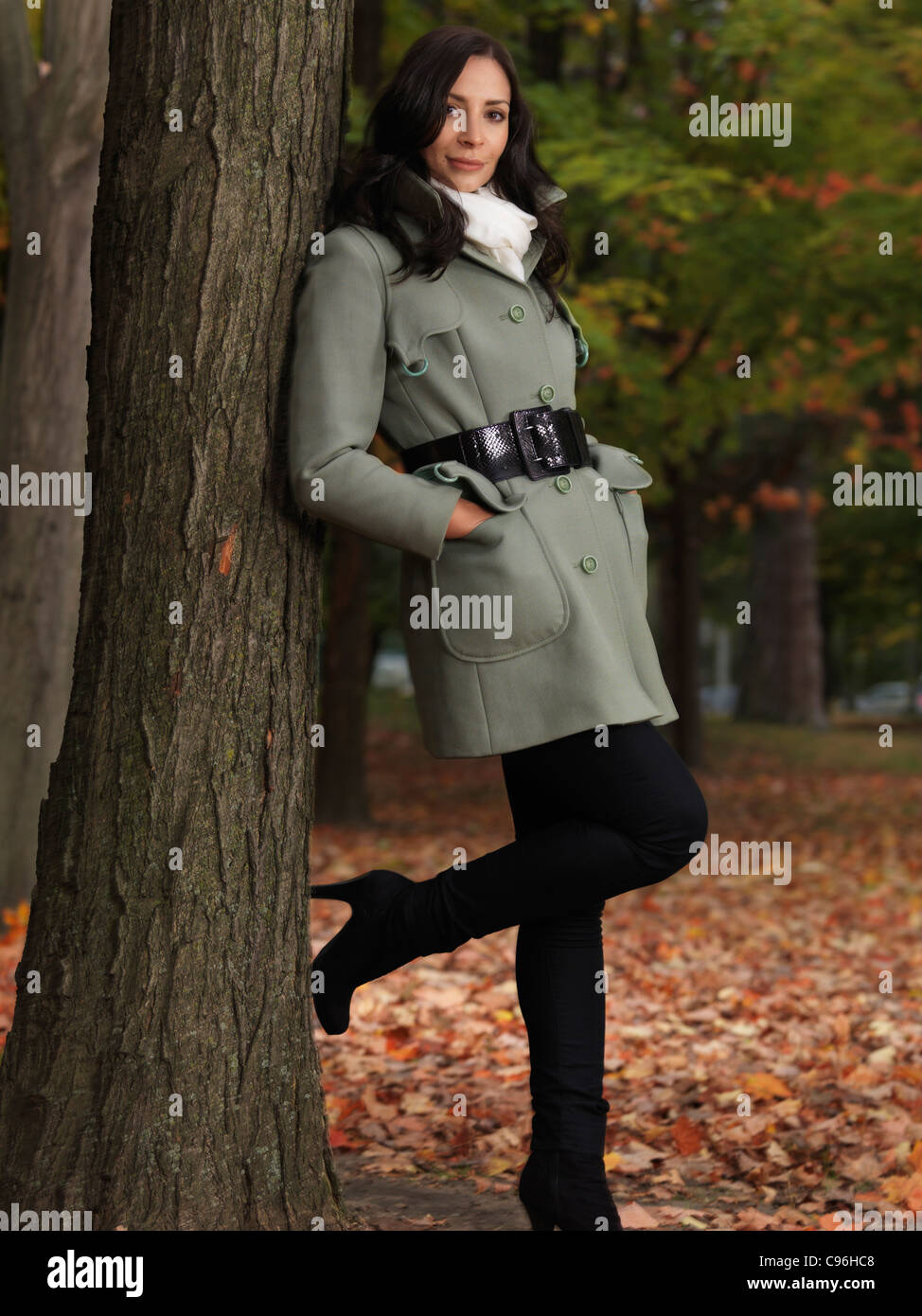 Fashionably dressed for autumn season, beautiful smiling young woman wearing a green coat, leaning against a maple - Stock Image