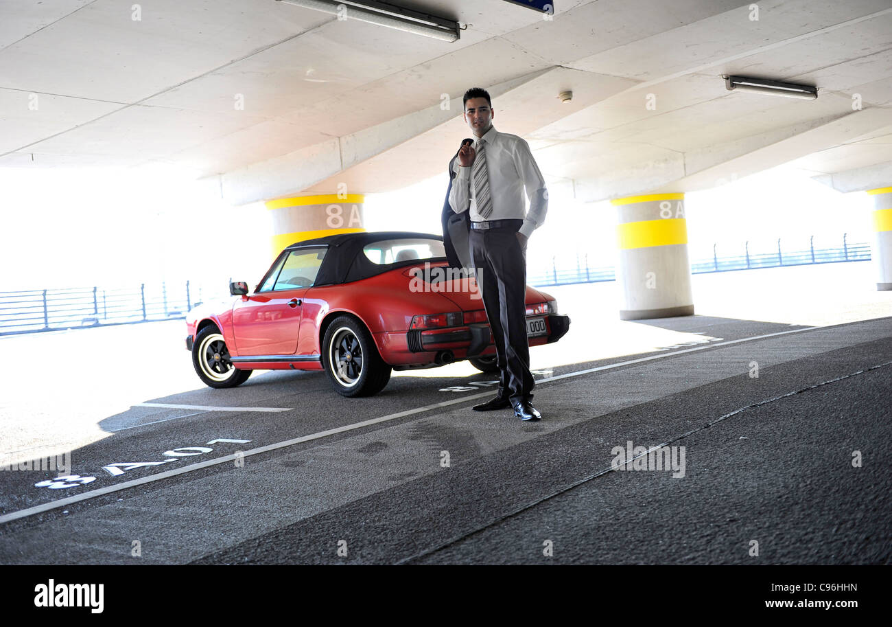 Young, self-confident businessman, wearing a suit and standing beside a Porsche in a car park - Stock Image