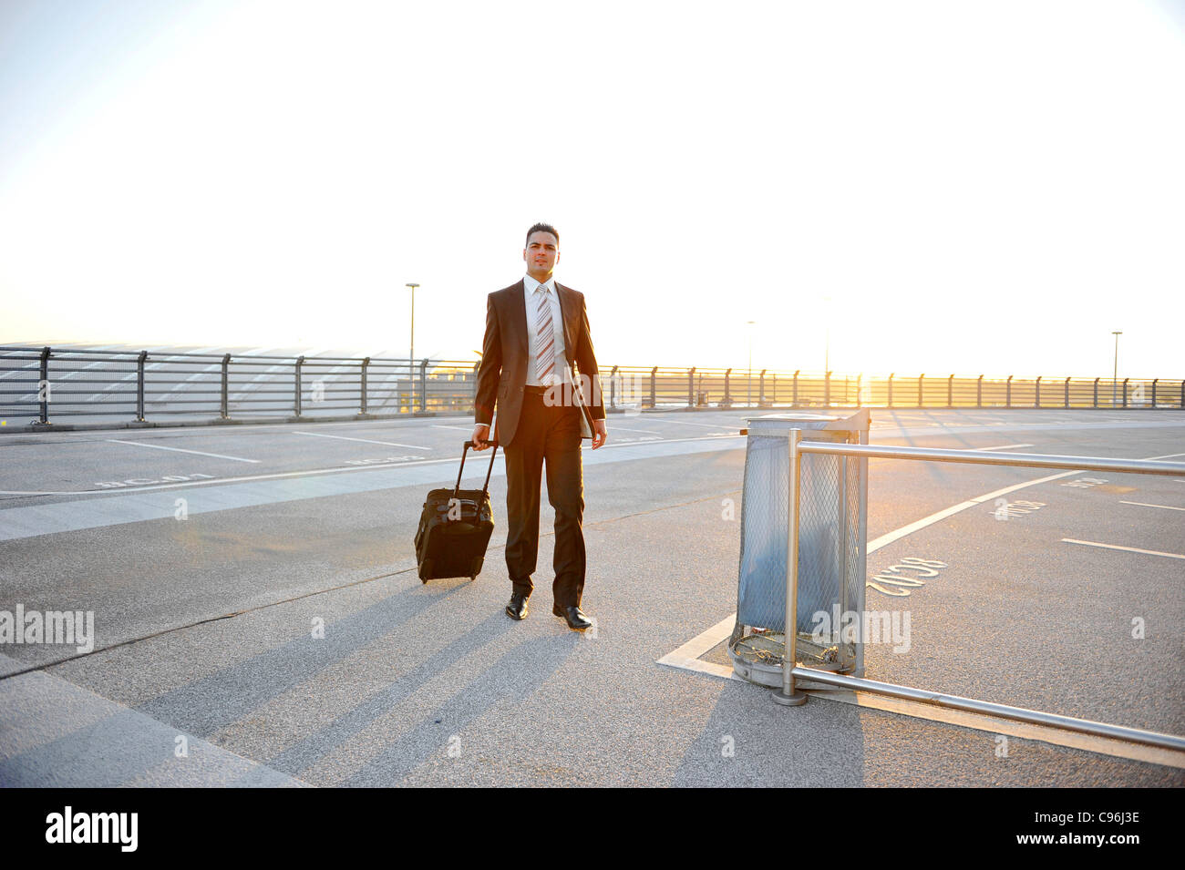 Young, self-confident businessman, wearing a suit and walking with luggage for a business trip at Airport, Hamburg, - Stock Image
