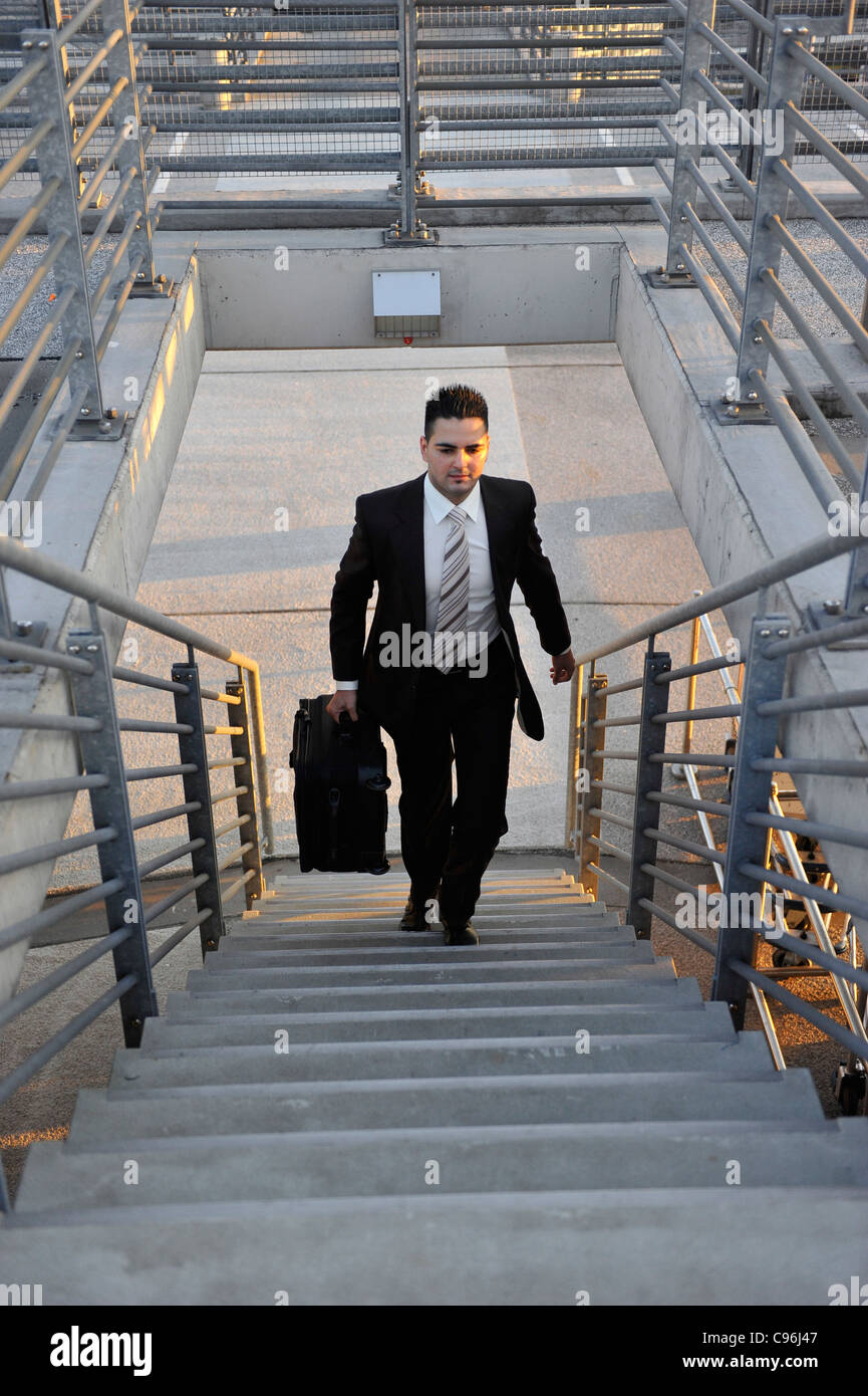 Young, self-confident businessman, wearing a suit and walking with luggage for a business trip at Hamburg Airport, - Stock Image