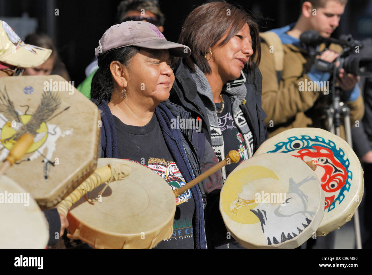 First Nations women banging ceremonial drums. - Stock Image