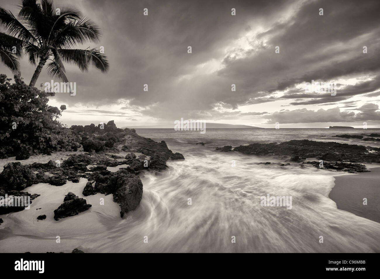 Sunset clouds and wave with palm trees. Maui, Hawaii. - Stock Image