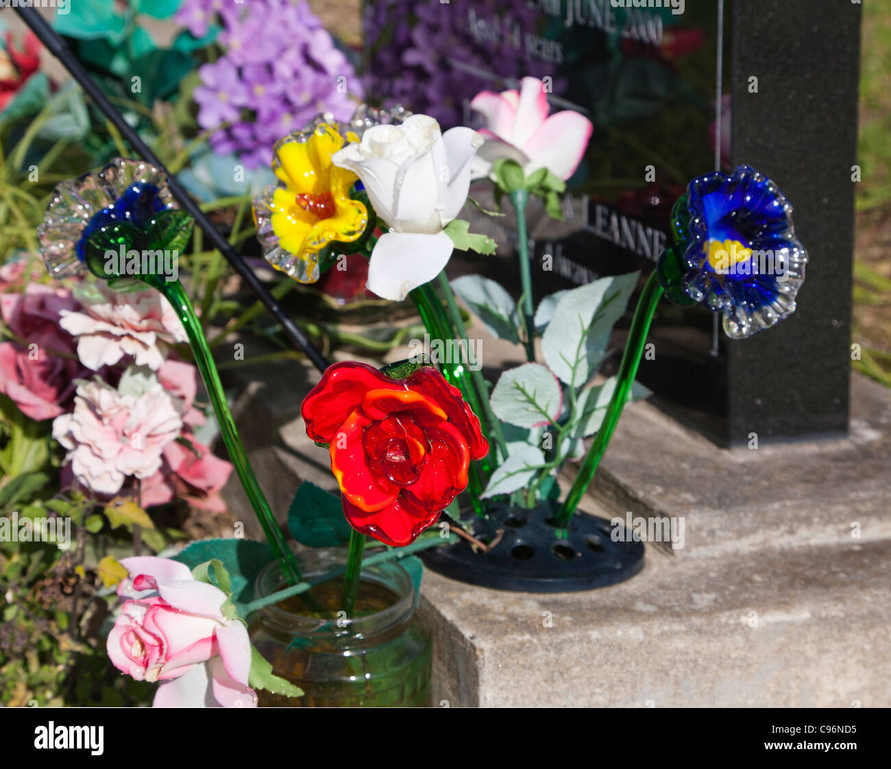 Detail of colourful glass and silk flowers beside a headstone on a detail of colourful glass and silk flowers beside a headstone on a grave cemetery mightylinksfo