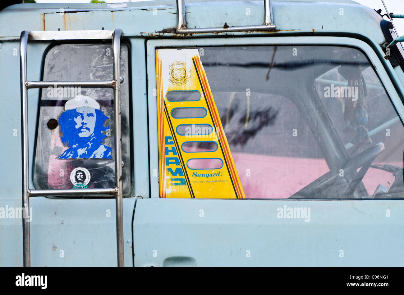 Side window of old light blue truck with 2 stickers of che guevara in window in thailand