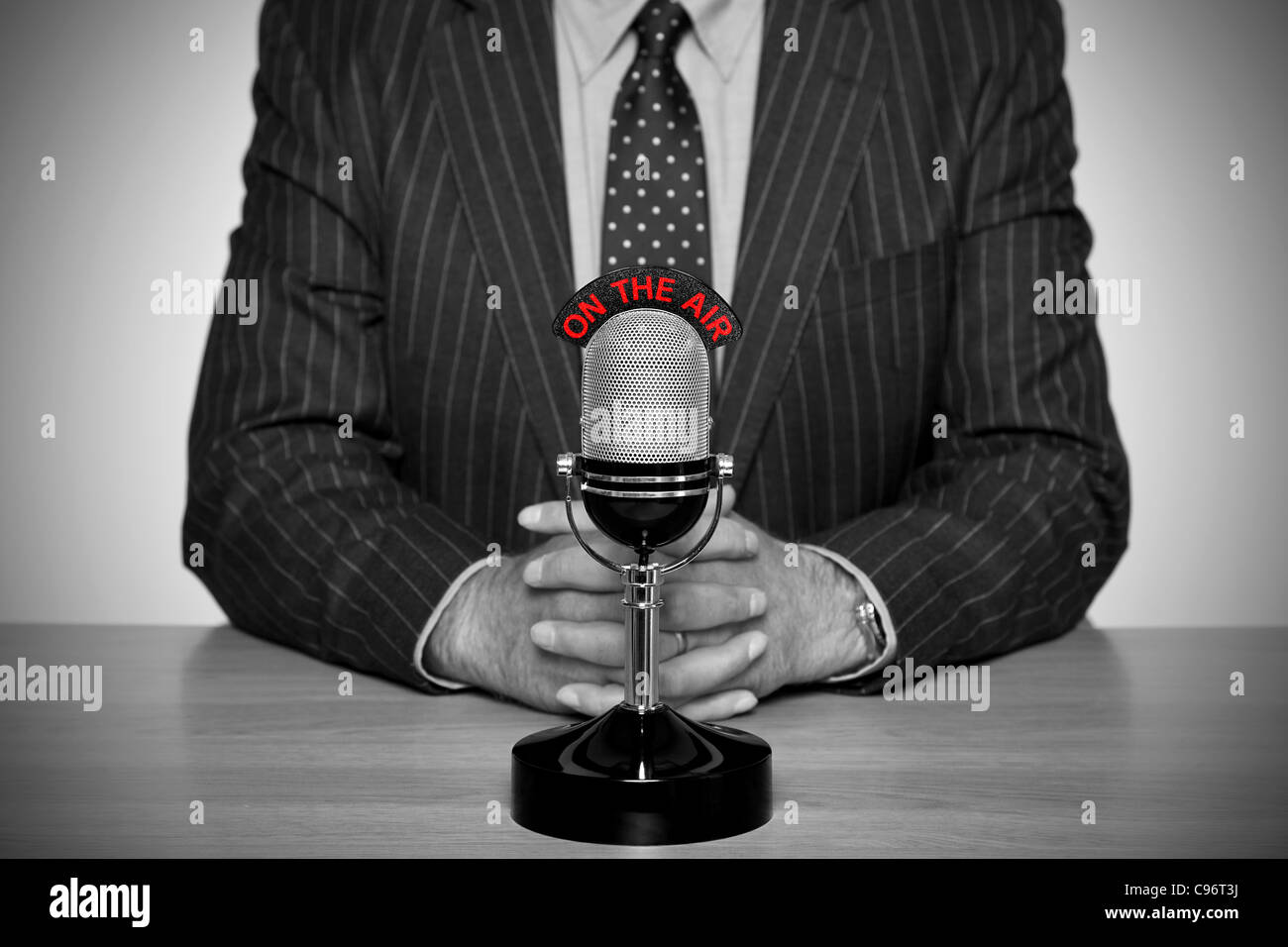 Photo of a news broadcaster sat at a desk and retro microphone with an On The Air illuminated sign - Stock Image