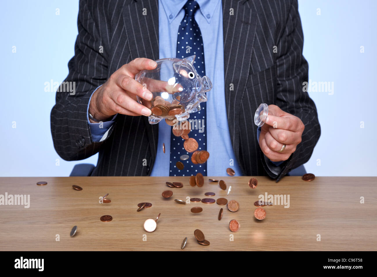 Photo of a banker sat at his desk emptying coins from his piggy bank. - Stock Image