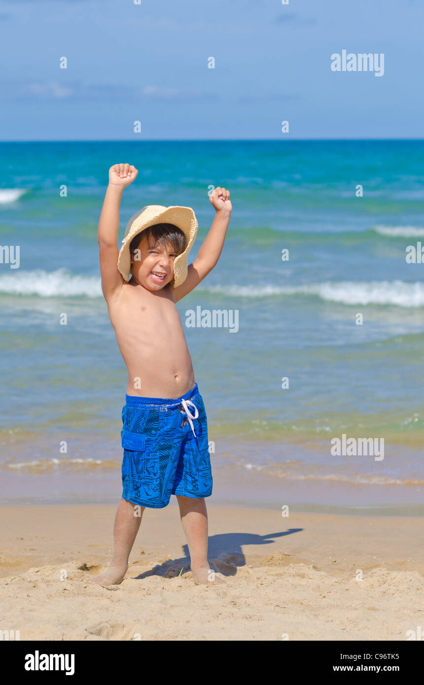 joyful kid with hat rising arms and yelling at beach - Stock Image