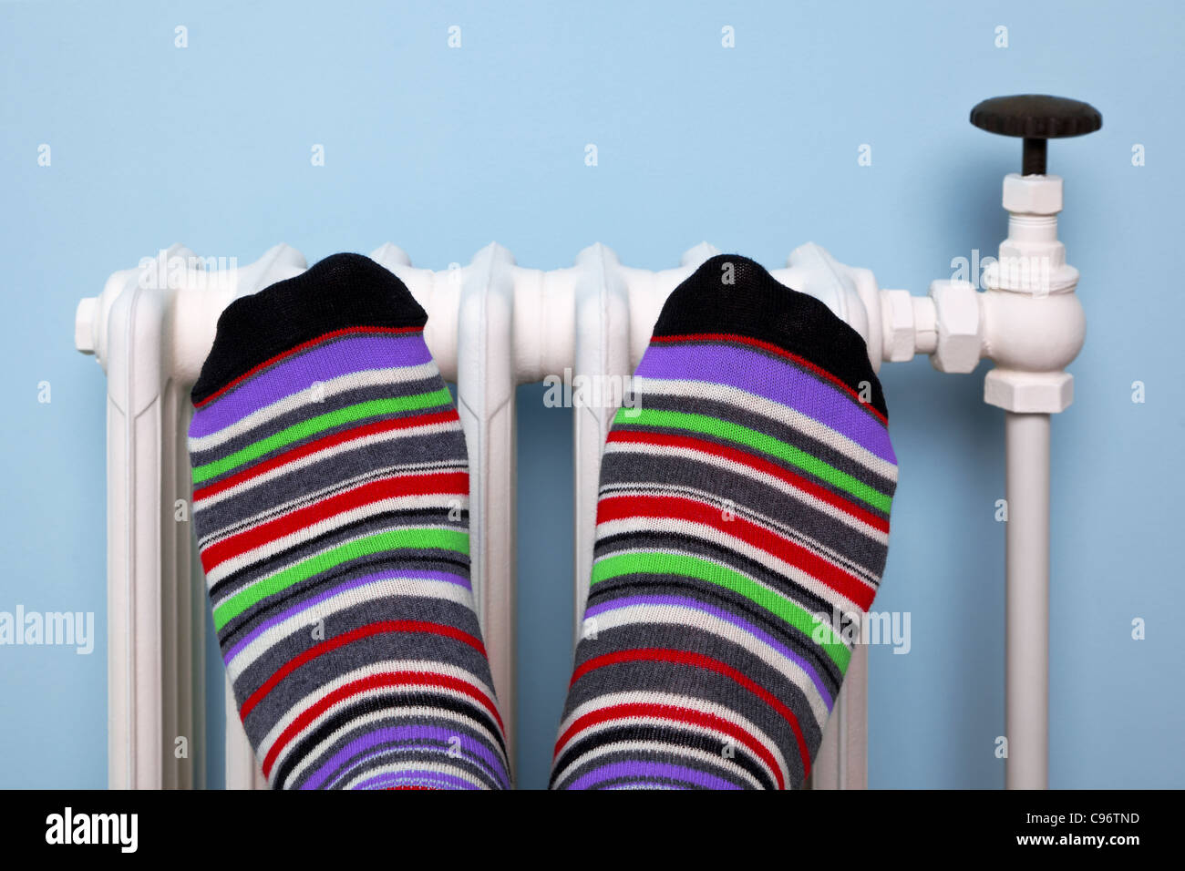 Photo of a persons feet in striped socks warming them against an old traditional cast iron radiator. - Stock Image