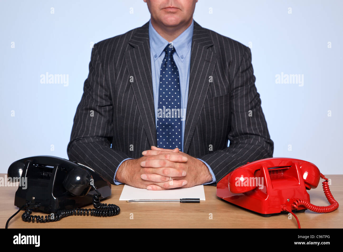 Photo of a businessman sat at a desk with two traditional telephones, one red and one black. - Stock Image