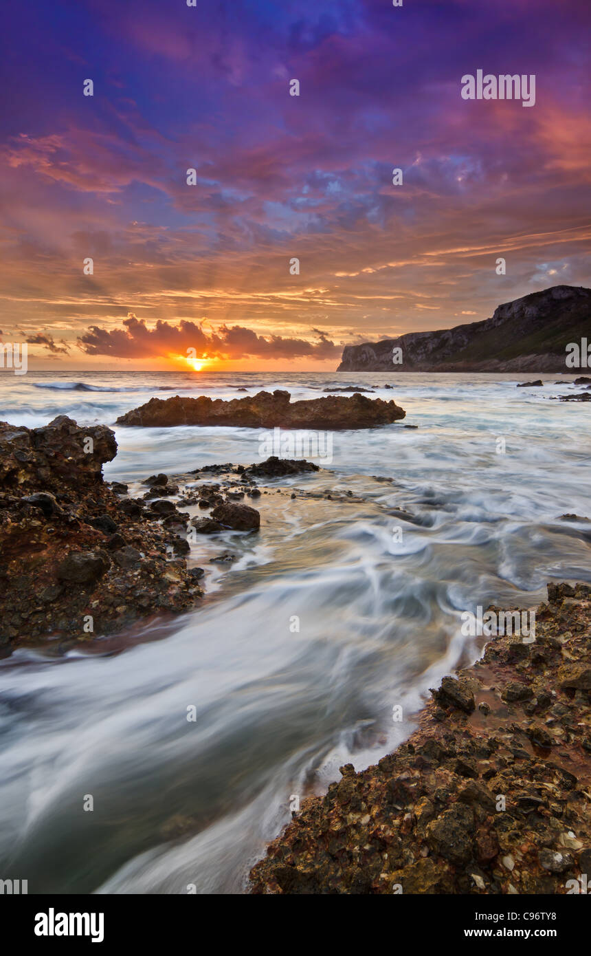 sunrise seascape with water in motion on the rocks and sunrays trough the clouds - Stock Image