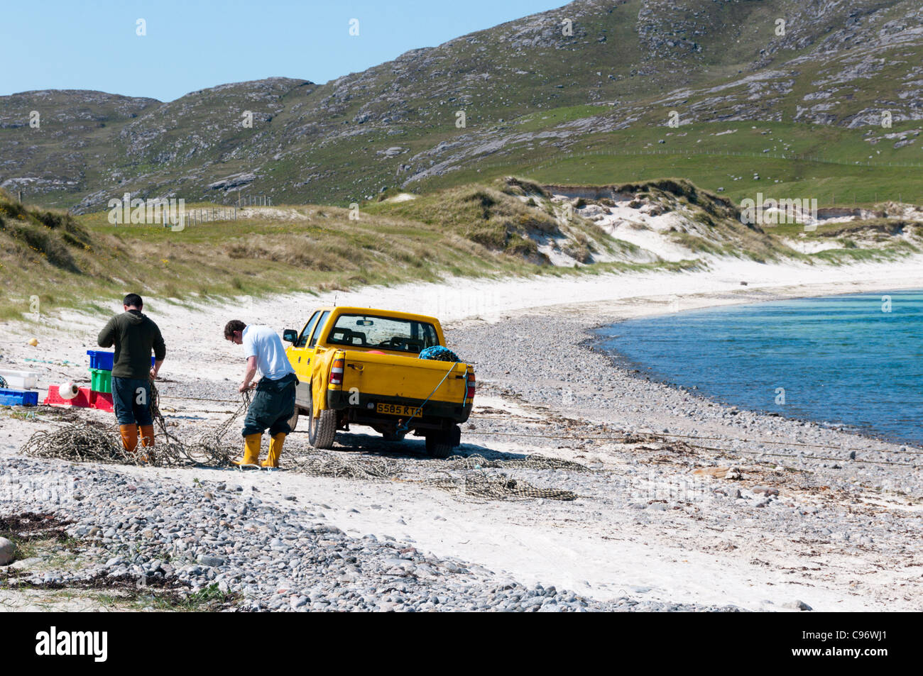 Two fishermen working next to a van parked on the beach at Vatersay in the Outer Hebrides. - Stock Image
